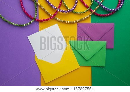 Multi color Mardi Gras beads and envelop with card on paper background.