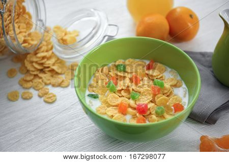 Tasty cornflakes with candied fruit on table