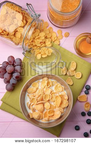 Tasty cornflakes with berries on pink background