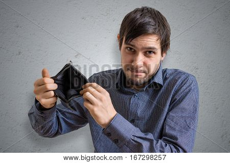 Bankruptcy and insolvency concept. Young man has no money and is showing empty wallet.