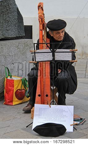Bratislava, Slovakia - November 4, 2015: old man is playing harp outdoor in Bratislava, Slovakia