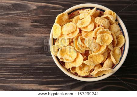 Bowl with cornflakes on wooden background