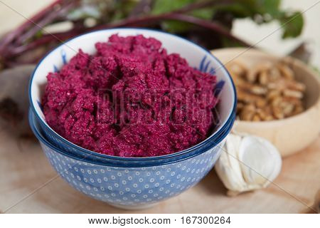 Beetroot pesto in a blue bowl on a wooden table with garlic beetroot on the back selective focus
