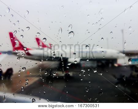 Airport window glass with raindrops in focus and row of airplanes blurred in background