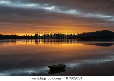 brilliant sunrise beyond silhouettes of hills and land provides a glow and reflections across Tauranga Harbor and small dinghy