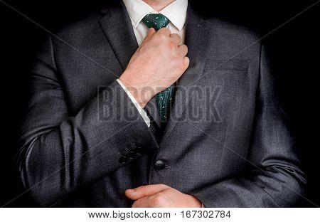 Businessman In Black Suit Adjusting His Tie