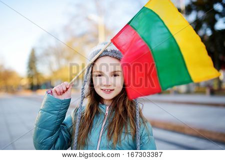Cute Little Girl Celebrating Lithuanian Independence Day Holding Tricolor Lithuanian Flags
