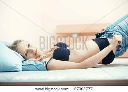 Blond lady laying on the bed and taking off jeans