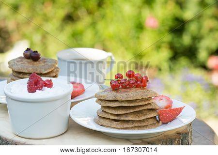 Breakfast in the garden: paleo style grain free banana almond pancakes coconut yogurt with berries selective focus on redcurrants