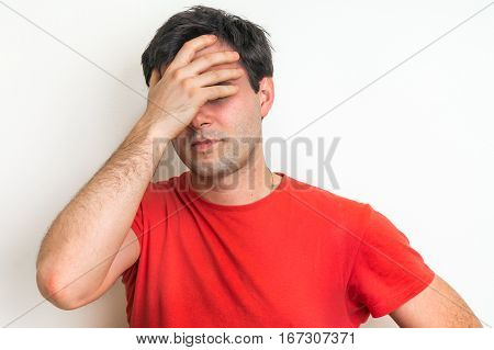 Disappointed man in depression with headache and negative face expression