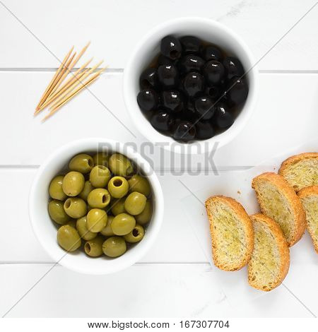 Pitted black and green olives in bowls with crostini on the side photographed overhead on white wood with natural light