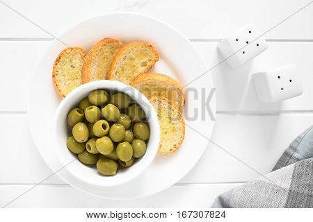 Pitted green olives in bowl with crostini on the side photographed overhead on white wood with natural light