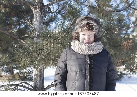 Portrait of smiling senior woman in a snow-covered winter park