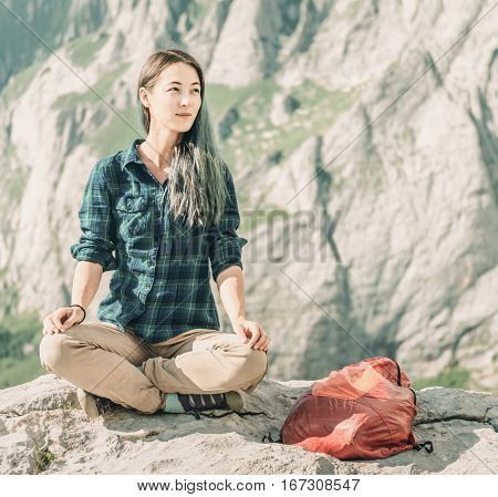 Smiling female explorer sitting in pose of lotos on stone in summer on background of rocks outdoor