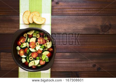 Fresh salad of black and green olives cherry tomatoes green bell pepper and cucumber seasoned with salt pepper dried oregano and basil served with crostini on the side photographed overhead on dark wood with natural light