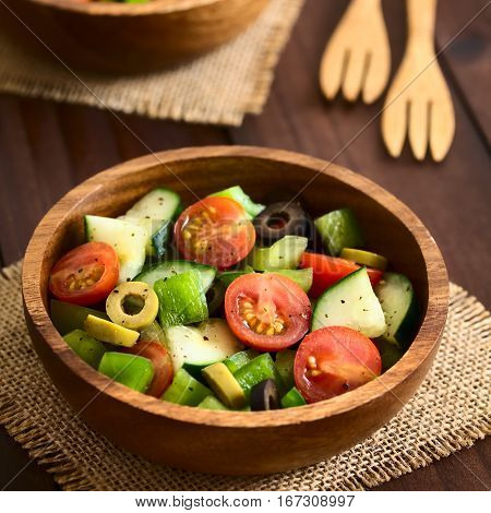 Fresh salad of black and green olives cherry tomatoes green bell pepper and cucumber seasoned with salt pepper dried oregano and basil served in wooden bowl photographed on dark wood with natural light (Selective Focus Focus in the middle of the salad)