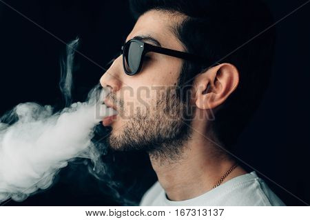 Young cool guy in sunglasses exhales a cloud of smoke. Studio horizontal portrait in profile close-up