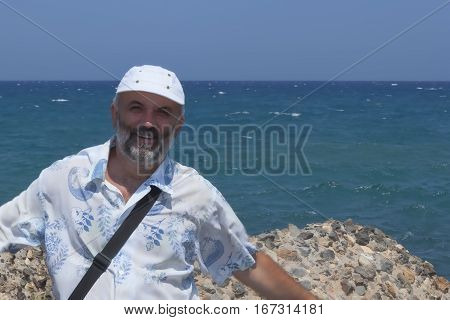 A middle aged man with a beard wearing a baseball cap on a hot summer day on the beach