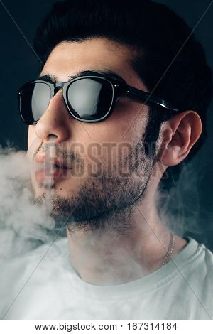 Young cool guy in sunglasses exhals a cloud of smoke. Vertical studio portrait in close-up.