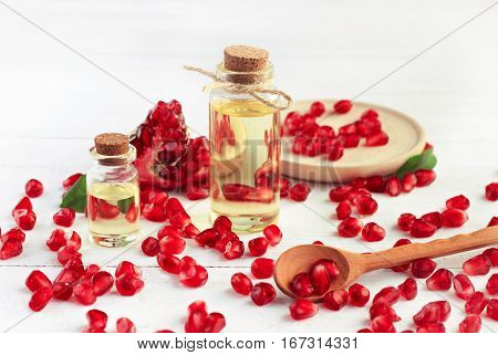 Pomegranate seed oil. Glass bottle of oil, ruby red fruit seeds, white table. Cosmetic skincare and culinary benefits.