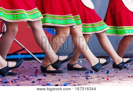 russian girls in traditional costumes dancing on stage outside. legs closeup