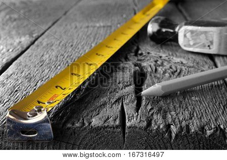 A low angle image of a yellow tape measure, hammer, and pencil on a wooden workbench - selective colour.