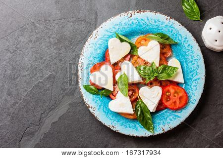 Mediterranean Italian Caprese salad with tomatoes and cheese mozzarella cut as hearts and basil on blue plate on slate background. Valentine day menu consept. Top view