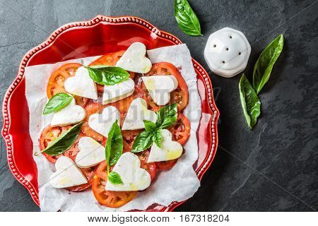Mediterranean Italian Caprese salad with tomatoes and cheese mozzarella cut as hearts and basil on red plate on slate background. Valentine day menu consept. Top view