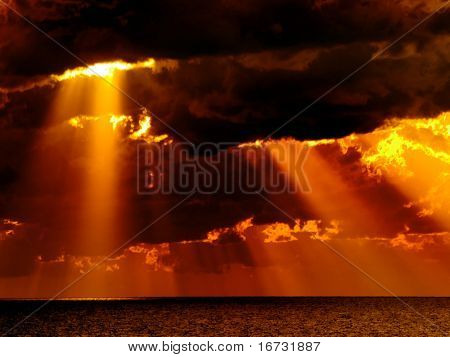 Dark clouds with sun rays over sea.