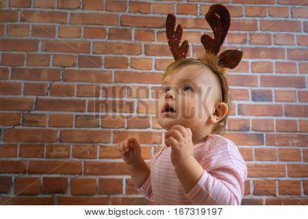 Mask the horns of a deer on funny little cute baby girl