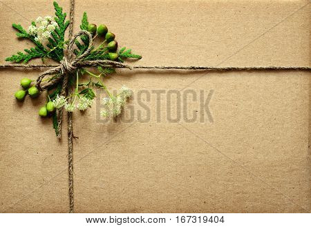 Wrapped box tied with rope and summer flowers and berries for background