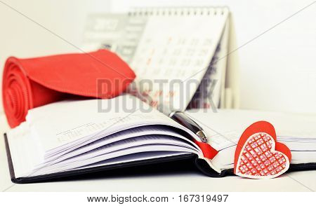 Pen necktie and a heart on opened notebook