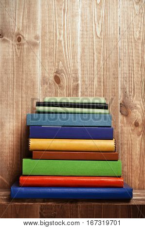 Pile of books on brown wooden shelf