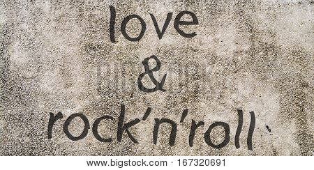 The gray concrete wall with the words love and rock-n-roll to create a background image.