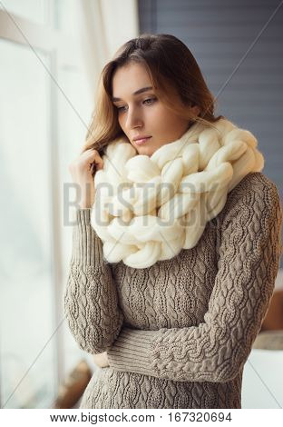 Beautiful sad young woman wearing merino wool pastel colors scarf in the warm atmosphere.