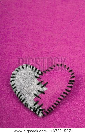 stitched broken felt heart on a on pink background