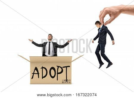 Small businessman sitting in a box marked 'Adopt' and looking up, while a giant hand brings another man to the box. Business and success. Business incubator. Startups.