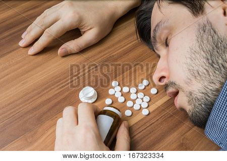 Overdose Of Pills. Man Is Lying On Table.