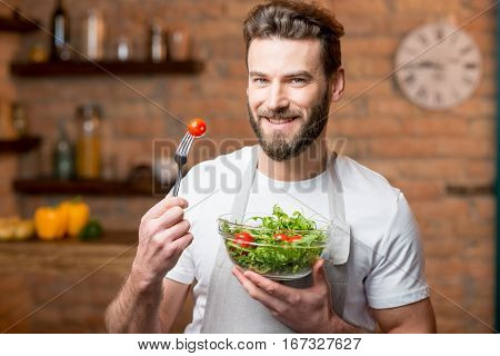 Handsome bearded man in white t-shirt and apron eating salad with tomatoes in the kitchen. Healthy and vegan food concept