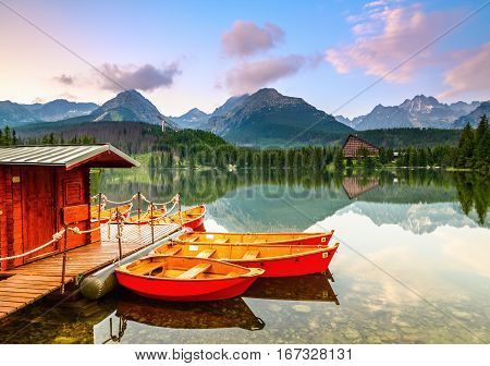 Red boats moored at wooden house on a lake with a clear water against the background of high mountains.Strbske Pleso lake Slovakia Tatra mountains.