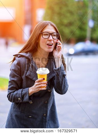 Girl in jacket talking on the phone, emotionally, shouting curses, holding a coffee or tea, a young outdoors, spring or autumn, lifestyle, concept anger