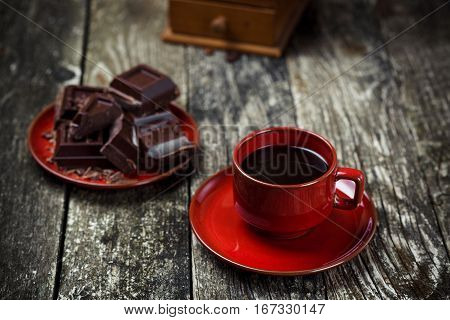Coffee red cup pieces of chocolate on the wooden table background. Tinted. Selective focus.