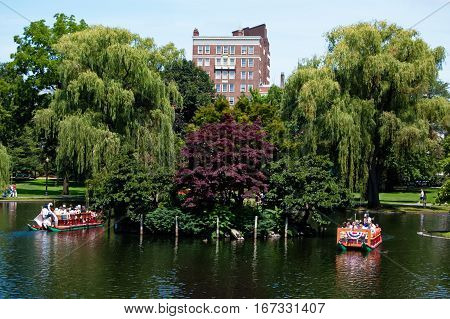 Boston, Massachusetts, US, 27 Jul. 2009: Tourists taking a ride on famous Swan Boats established in 1877 in Boston Public Garden.