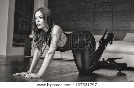 Sexy dominatrix woman kneeling on floor with whip black and white indoor bdsm