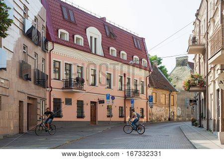 Vilnius Lithuania - September 11 2016: Unidentified people ride their bikes at picturesque Odminiu street in Vilnius old town.