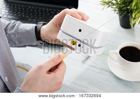 Businessman connects his laptop to the mobile WiFi router with LAN cable