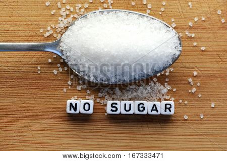 No sugar phrase made from plastic letter cubes and a spoon full of sugar