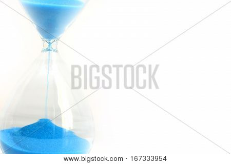 Hourglass with running blue sand suggesting passage of time