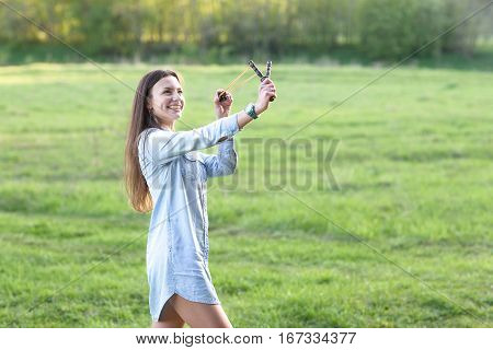 Woman using a slingshot. Over meadow background