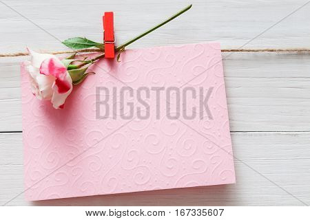 Valentine background, empty greeting card and rose flower on clothespin on white rustic wood planks. Happy lovers day card mockup, copy space